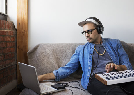 Man using laptop computer with piano at home - CAVF32981