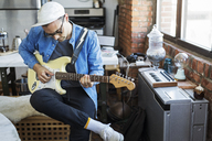Man playing guitar at home - CAVF32996