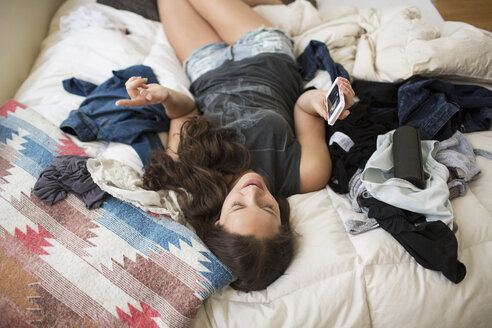 High angle view of playful woman using smart phone while lying on bed at home - CAVF33008