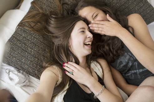 Overhead view of female friends laughing while lying on bed at home - CAVF33014