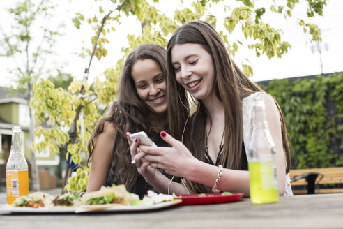 Smiling female friends using smart phone while sitting at sidewalk cafe - CAVF33020