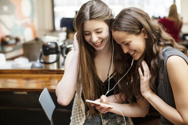 Smiling female friends using smart phone while sitting in cafe - CAVF33023