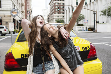 Cheerful female friends sitting on yellow taxi on road in city - CAVF33026