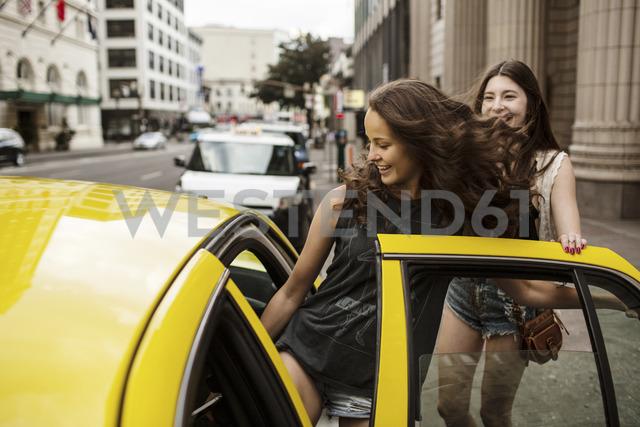 Smiling female friends entering in taxi - CAVF33029 - Cavan Images/Westend61