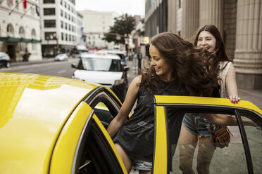 Smiling female friends entering in taxi - CAVF33029
