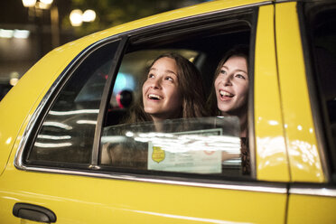 Smiling female friends looking through window while traveling in taxi - CAVF33041
