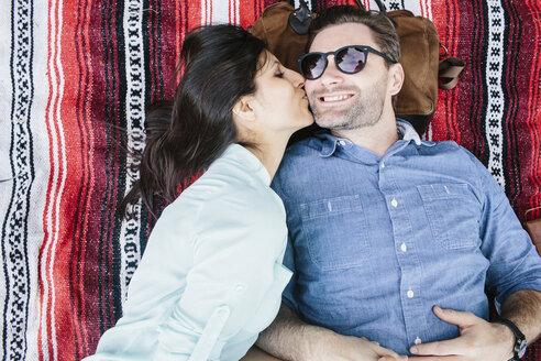 Overhead view of girlfriend kissing boyfriend while lying on blanket in park - CAVF33044