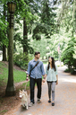 Happy couple holding hands and walking on footpath with dog at park - CAVF33047