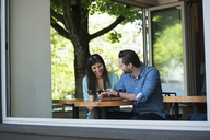 Happy couple looking at mobile phone while sitting in cafe seen through window - CAVF33050
