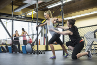 Instructor assisting woman in pulling resistance bands at health club - CAVF33098