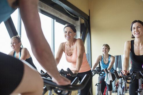 Midsection of male instructor guiding smiling women cycling on exercise bikes at gym - CAVF33143