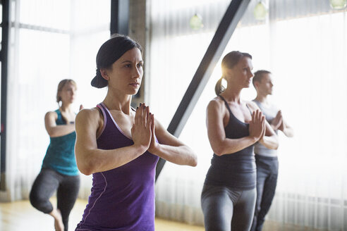Male instructor with women practicing tree pose in health club - CAVF33164