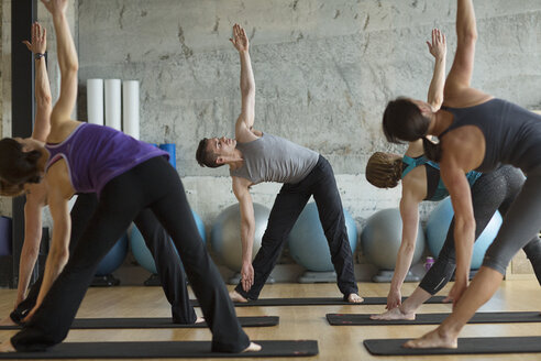 Male instructor guiding women in doing triangle position in gym - CAVF33167