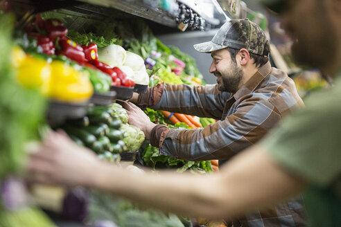 Workers arranging vegetables at supermarket - CAVF33182