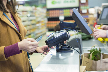 Midsection of woman paying bill with credit card while standing by counter at supermarket - CAVF33191