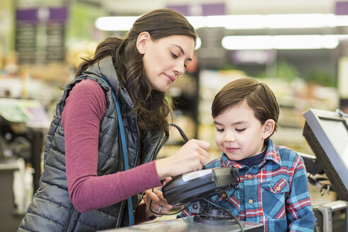 Mother with son at checkout counter in supermarket - CAVF33197