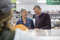 Smiling couple standing by counter at supermarket - CAVF33215