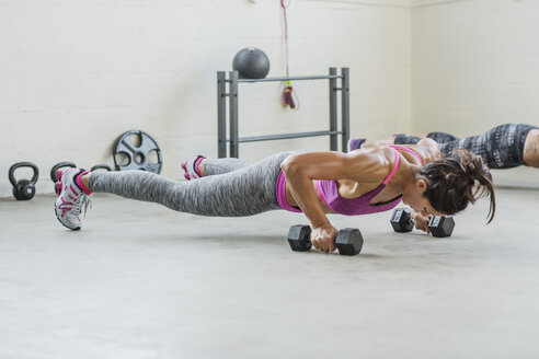Female athletes holding dumbbells and doing push-ups in gym - CAVF33275