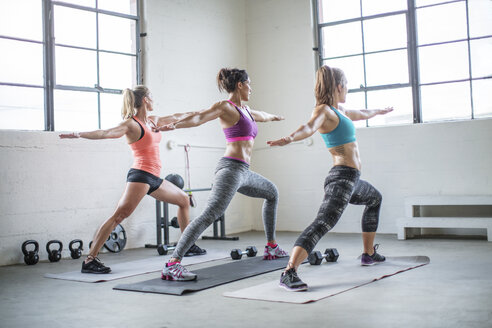 Female athletes practicing warrior 2 pose in gym - CAVF33302