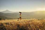 Full length of woman jogging on mountain against clear sky - CAVF33326