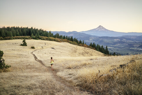 High angle view of woman jogging on mountain against clear sky during sunset - CAVF33329