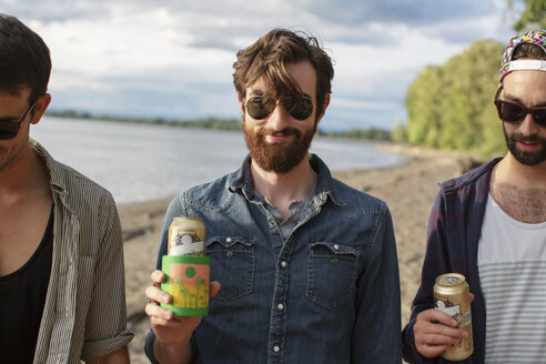 Male friends holding cans while standing at riverbank - CAVF33401