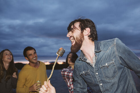 Smiling friends looking at man singing while holding roasted marshmallow on stick against cloudy sky - CAVF33437