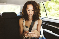 Woman using mobile phone while traveling in car - CAVF33446