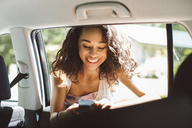 Smiling woman using mobile phone while leaning on car window - CAVF33449