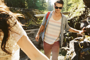 Cropped hand of woman hiking with male friend in forest - CAVF33464