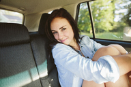 Portrait of smiling woman traveling in car - CAVF33473