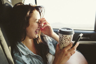Happy woman with coffee cup using mobile phone while traveling in car - CAVF33476
