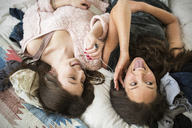 High angle view of playful female friends listening music while lying on bed at home - CAVF33479
