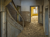 Africa, Namibia, inside a house of ghost town Kolmanskop, wooden door and sand - RJ00754