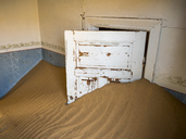 Africa, Namibia, inside a house of ghost town Kolmanskop, wooden door and sand - RJ00757