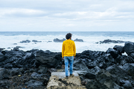 Azores, Sao Miguel, rear view of man looking at the sea from stony coast - KIJF01914