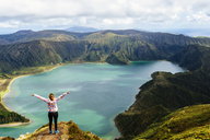 Azores, Sao Miguel, Woman with raised arms on the top of the Lagoa do Fogo - KIJF01917