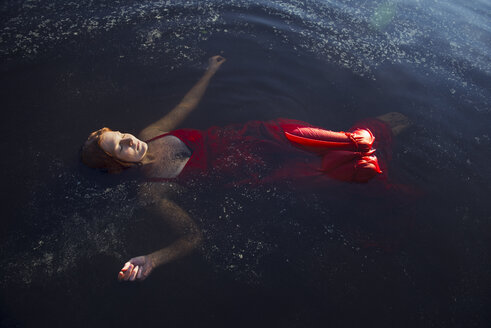 Woman in red dress floating on water - FOLF06626