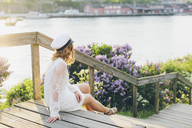 Woman sitting on wooden boardwalk - FOLF06707