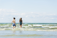 Girl and boy walking into sea - FOLF06716