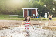 Girl splashing water and boy standing on ground - FOLF06722