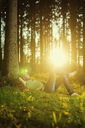 Man sleeping by tree in spruce forest - FOLF06800