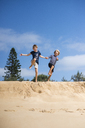 Two boys jumping from sand dune on beach - FOLF06824