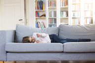 Girl lying on couch at home holding cell phone - LVF06848