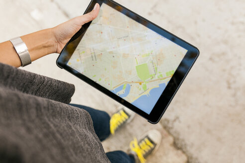 Close-up of woman holding tablet with digital street map - VABF01523