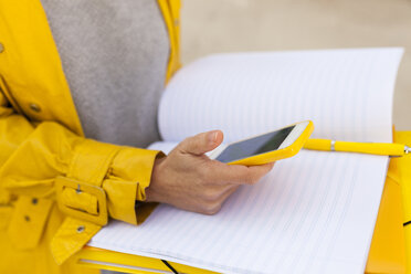 Close-up of woman with cell phone and folder outdoors - VABF01532