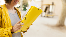 Close-up of smiling woman holding yellow folder outdoors - VABF01535