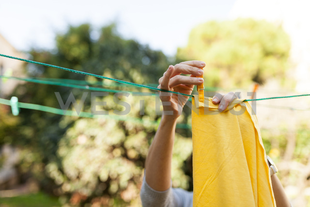 Close-up of woman hanging up yellow blanket on clothesline - VABF01544 - Valentina Barreto/Westend61