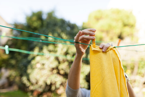 Close-up of woman hanging up yellow blanket on clothesline - VABF01544