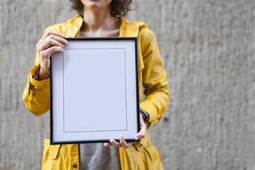 Close-up of woman holding blank frame - VABF01547